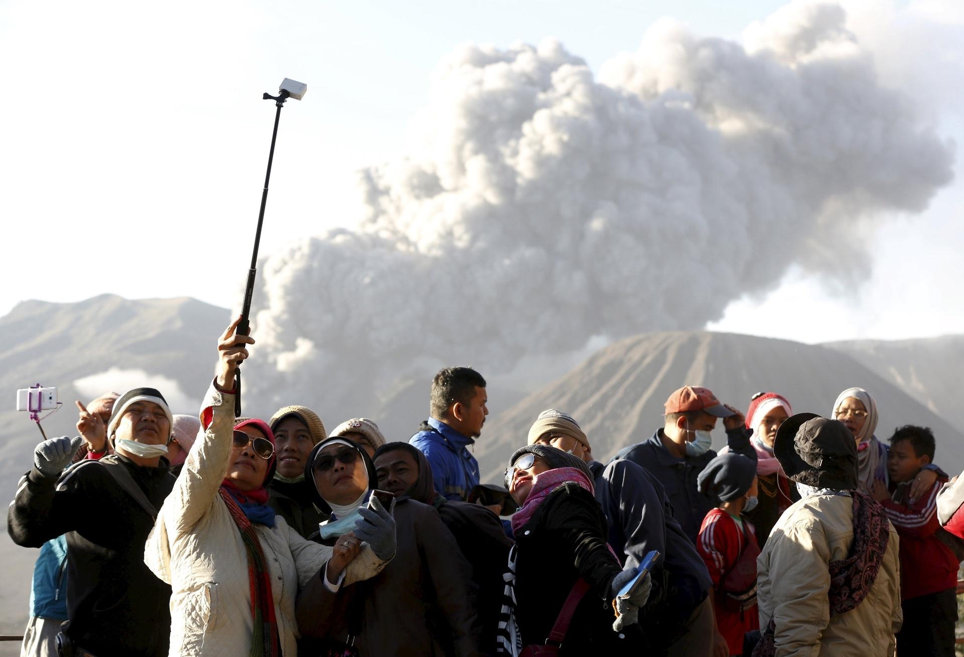 6.jan.2016 - Turistas fazem selfie com o vulcão Bromo em erupção ao fundo, próximo a Ngadisari, na Indonésia