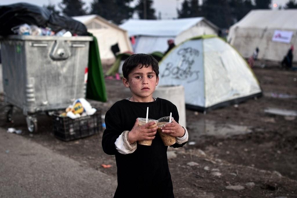 1°.mar.2016 - Menino refugiado carrega dois copos com a comida que recebeu em um acampamento improvisado feito em Idomeni, na Grécia, onde milhares de imigrantes aguardam a liberação da fronteira Macedônia para entrar em outros países da Europa