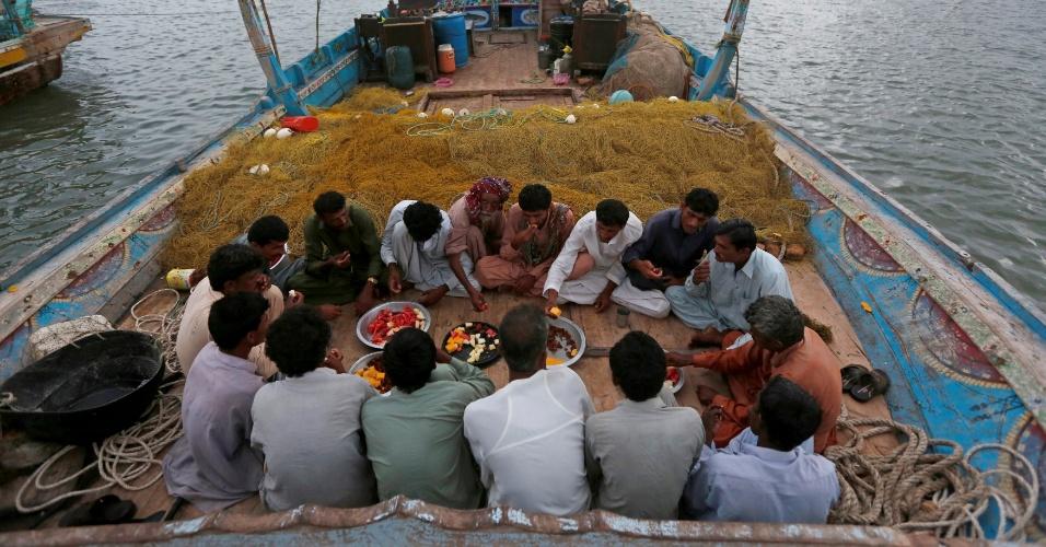 """4.jul.2016 - Pescadores comem o iftar em um barco durante o mês sagrado do Ramadã em Ibrahim Hyderi, nos arredores de Karachi, no Paquistão. Um deles, Haji Husain, 65, disse que o Ramadã """"significa jejuar e fazer boas ações, o que te mantém longe de Satanás"""""""