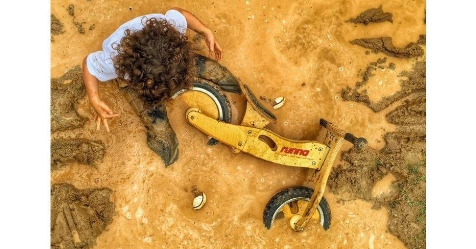 """Entre aqueles que receberam distinções estão alguns latino-americanos. O brasileiro Bruno Dreux foi premiado com o terceiro lugar na categoria """"Crianças"""" pelo retrato de Felipe, seu filho de três anos, que gosta de explorar a pista de motocross em sua bicicleta de madeira. """"Nesse dia em particular, estava tão emocionado pelo lodo e pela chuva que não pôde resistir a saltar na poça d'água"""", conta."""