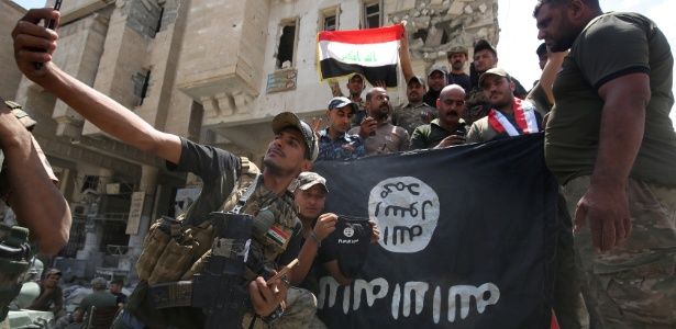 8.jul.2017 - Integrantes das forças iraquianas posam para foto com a bandeira do Estado Islâmico de ponta-cabeça em Mosul