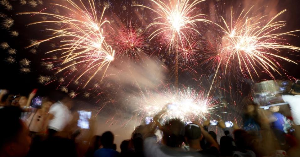 31.dez.2017 - Filipinos assistem fogos de artifício iluminando o céu neste Ano Novo, em Manila. Horas antes da meia-noite, autoridades divulgaram que dezenas de pessoas estavam feridas por conta de fogos de artifício
