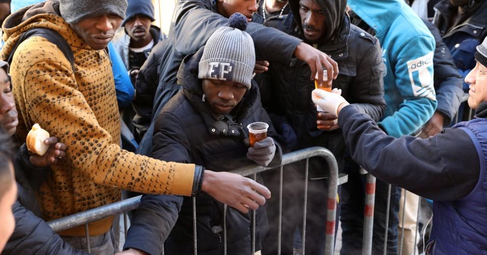 Voluntários da Caritas dão chá e pão a um grupo de imigrantes na cidade italiana Ventimiglia