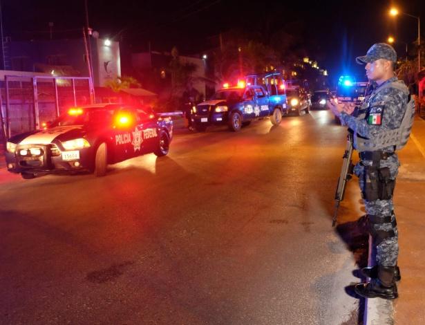 Oficial da polícia federal mexicana faz segurança da área onde houve tiroteio em Cancún - Pedro Pardo/AFP Photo
