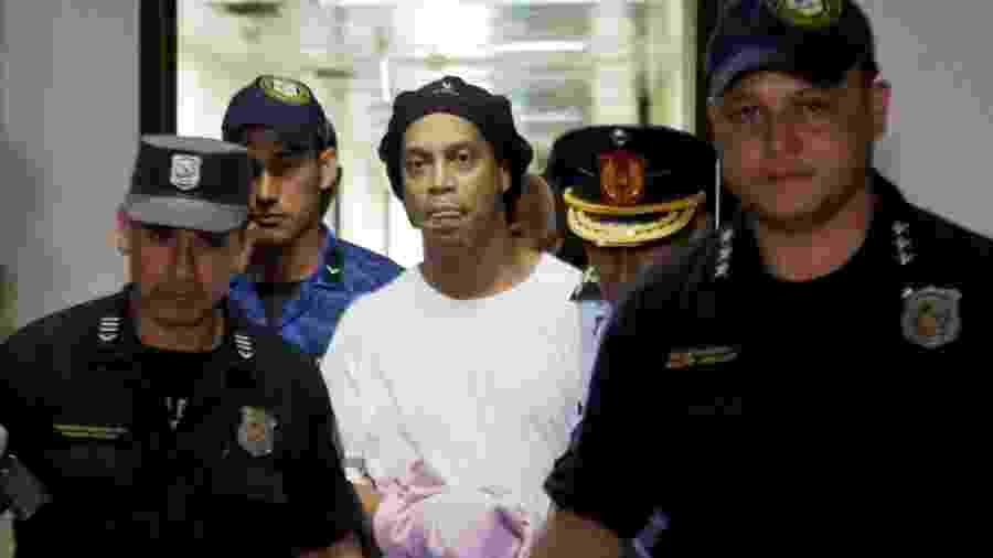 Ronaldinho é escoltado pela polícia em tribunal do Paraguai - JORGE ADORNO