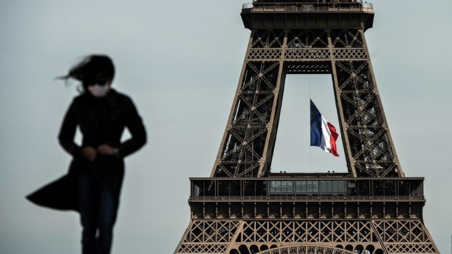 De máscara, mulher caminha em frente a Torre Eiffel, em Paris (França) - Philippe Lopez/AFP
