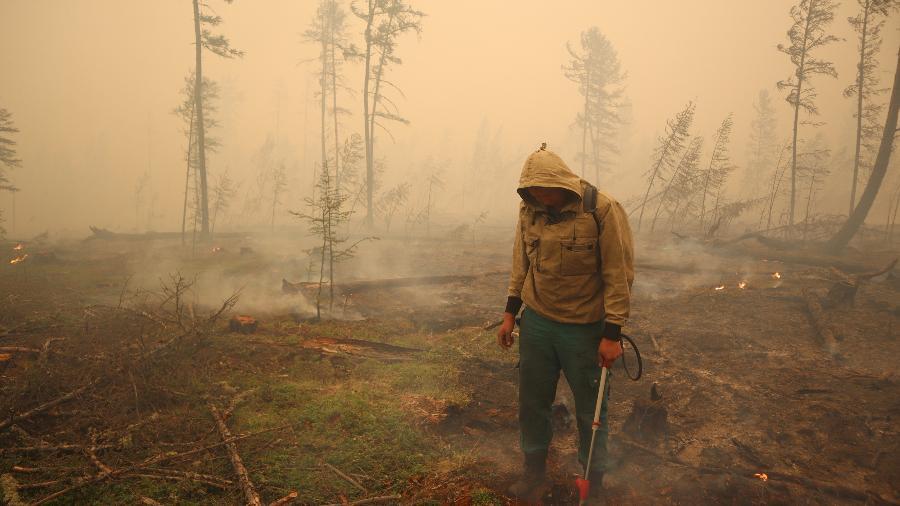 Funcionário de proteção florestal tenta combater incêndios em um vilarejo na região de Yakutia, na Rússia - REUTERS/Roman Kutukov