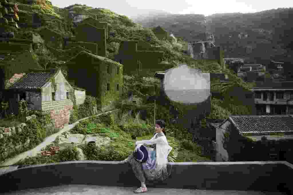 30.jul.2015 - Turista posa para foto em mirante da aldeia abandonada de Houtouwan, na ilha de Shengshan, na China. Apenas algumas pessoas ainda vivem no local, que já foi o lar de mais de 2.000 pescadores. Todos os dias, centenas de turistas percorrem as trilhas estreitas entre os últimos casebres que foram tomados pelas plantas. A fauna da região também reduziu caminhos e tornou inacessíveis algumas áreas. A vila remota, em uma das mais de 400 ilhas do arquipélago Shengsi, foi abandonada no início de 1990 primeiro pelos moradores ricos, que queriam escapar do cotidiano em que o acesso à educação e aos bens comuns era difícil. Em seguida, o restante da população foi deixando o local gradualmente - Damir Sagolj/Reuters