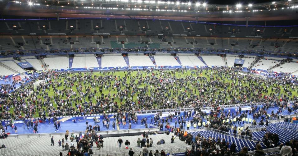13.nov.2015 - Torcedores se aglomeram no campo do estádio Stade de France, em Saint Denis, nos arredores de Paris. A polícia relatou ao menos duas explosões nas proximidades do estádio, onde o presidente francês, François Hollande, acompanhava um amistoso entre as seleções de futebol da França e da Alemanha. Três tiroteios aconteceram na noite desta sexta-feira (13) em Paris. De acordo com a polícia, há ao menos 18 mortos e vários feridos