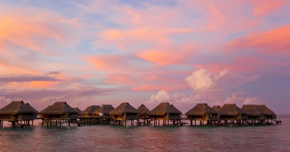 Um lugar para descansar e explorar. Um pôr do sol rosa e avermelhado toma conta do céu na ilha Moorea, na Polinésia Francesa. A pitoresca variedade topográfica da ilha inclui montanhas vulcânicas e praias tranquilas