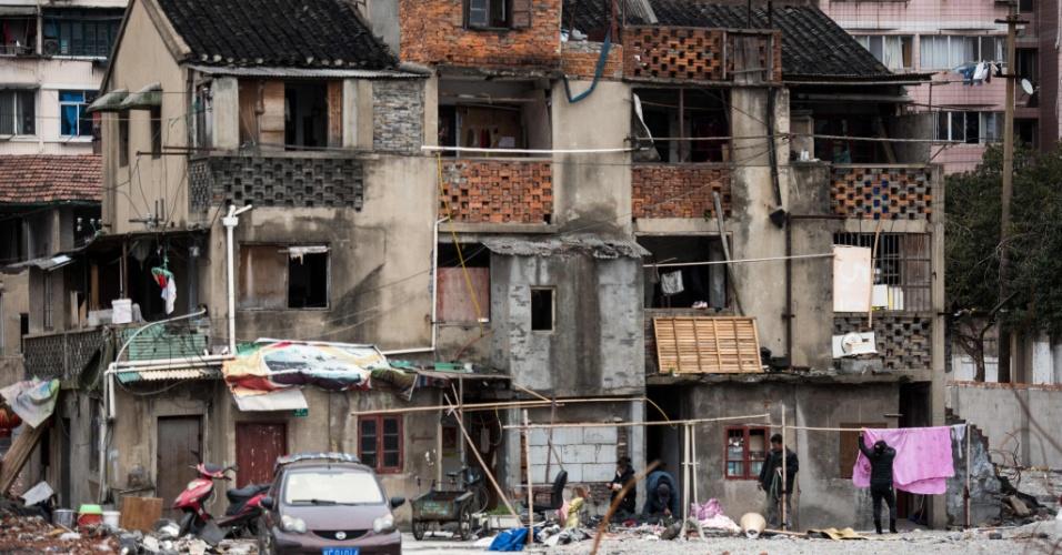 10.mar.2016 - Chinesa pendura roupas para secar diante de conjunto residencial que está agendado para ser demolido, no centro de Xangai (China)