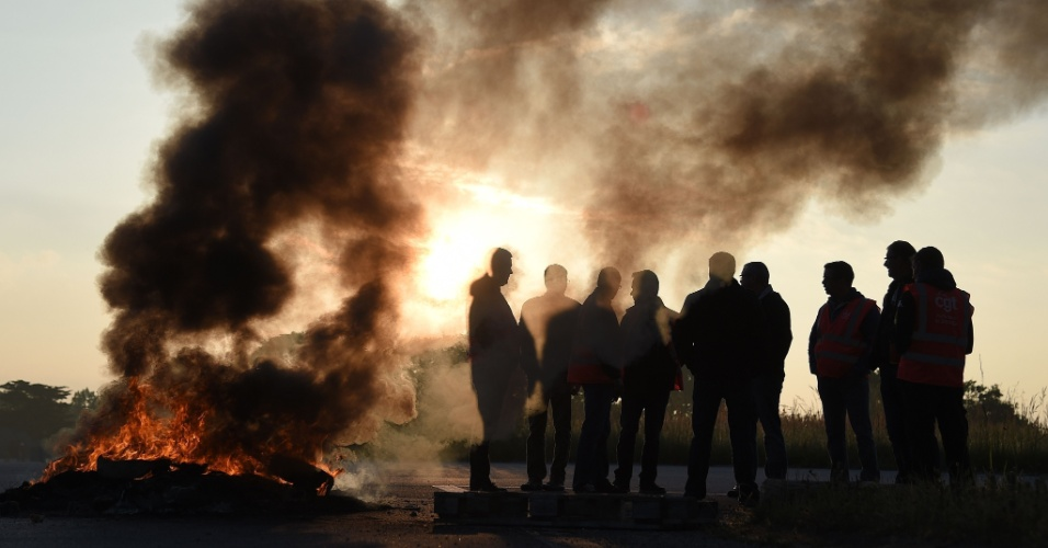 17.mai.2016 - Trabalhadores em greve colocam fogo em pneus para interditar estrada de acesso a refinaria em Donges, no oeste da França. O protesto é contra o projeto do governo de reforma das leis trabalhistas no país