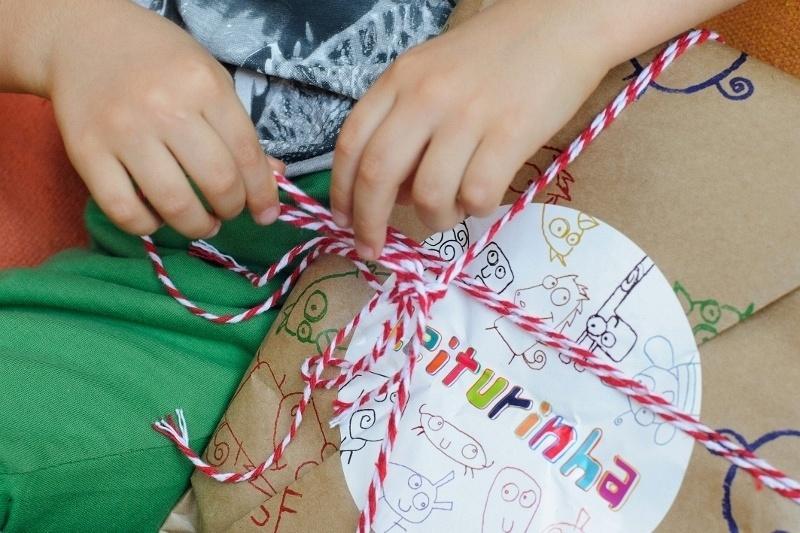 Criança abre pacote que recebeu do Leiturinha, clube de assinatura de livros infantis