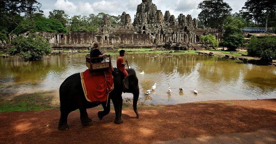 Turistas passeiam de elefante no templo de Bayon, no Camboja. Localizado na antiga cidade de Angkor Thom, o impressionante templo é coberto por mais de 200 rostos misteriosos esculpidos em pedra