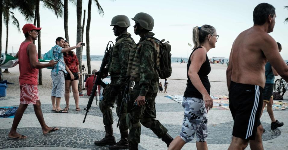 14.fev.2017 - Cariocas e turistas mantêm a rotina durante o patrulhamento de equipes do Exército na praia de Copacabana