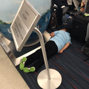 Garoto dorme no chão do aeroporto após voo de NY para SP ser cancelado; ele passou mal devido ao calor dentro da aeronave e descansou no chão até os passageiros serem deslocados para hotel