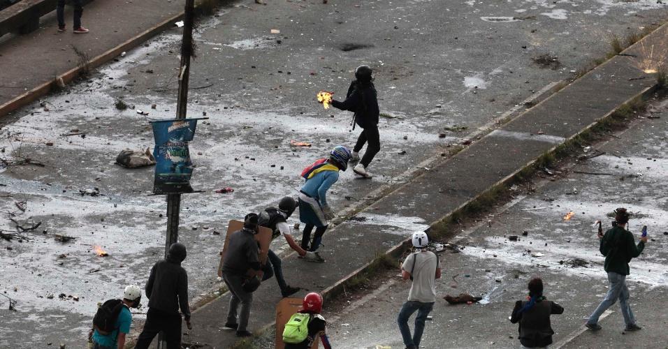30.jul.2017 - Manifestante lança coquetel molotov em confronto contra eleição