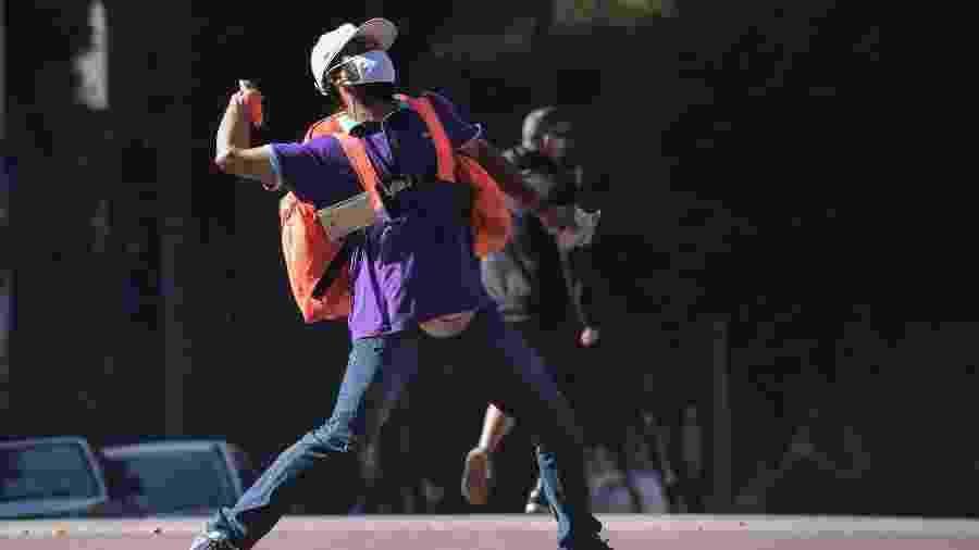 Entregador atira objeto durante manifestação na avenida Paulista, em São Paulo - Nelson Almeida/AFP