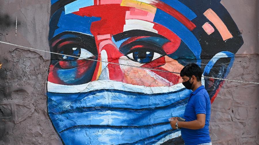 20.abr.2021 - Pedestre passa por mural que mostra pessoa usando máscara em Mumbai; Índia relata número recorde de mortes diárias de covid-19  - Punit Paranjpe/AFP