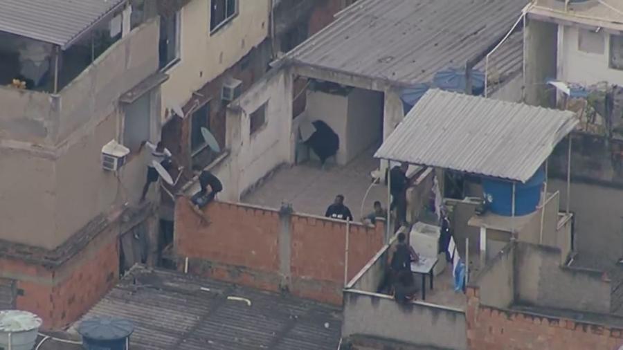Homens pulam entre casas durante operação no Jacarezinho, no Rio de Janeiro - Reprodução/Rede Globo