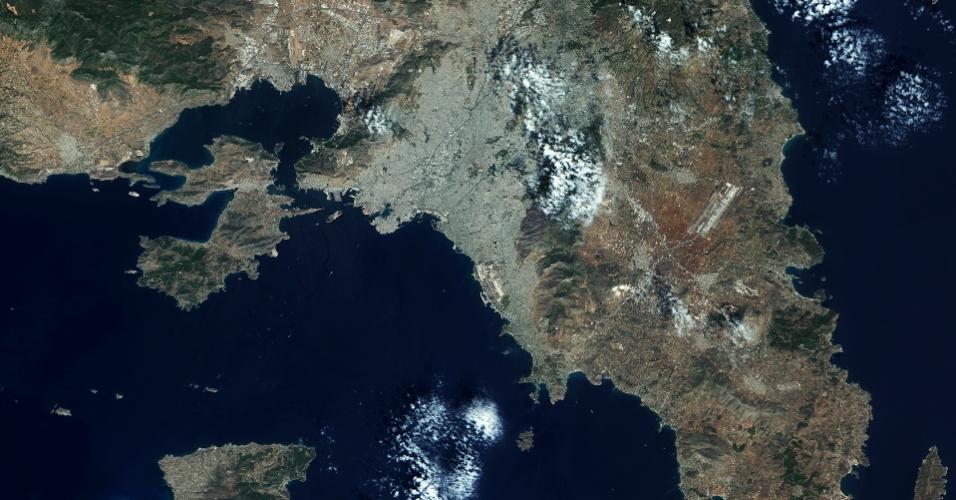 25.set.2015 - O satélite Sentinel 2A, da Esa (Agência Espacial Europeia), mostra a capital grega Atenas e arredores. A cidade aparece na parte acinzentada, apoiada por montanhas esverdeadas em sua borda oriental. O Aeroporto Internacional de Atenas pode ser visto mais a leste, cercado por campos agrícolas, que são retratados em tons de avermelhados
