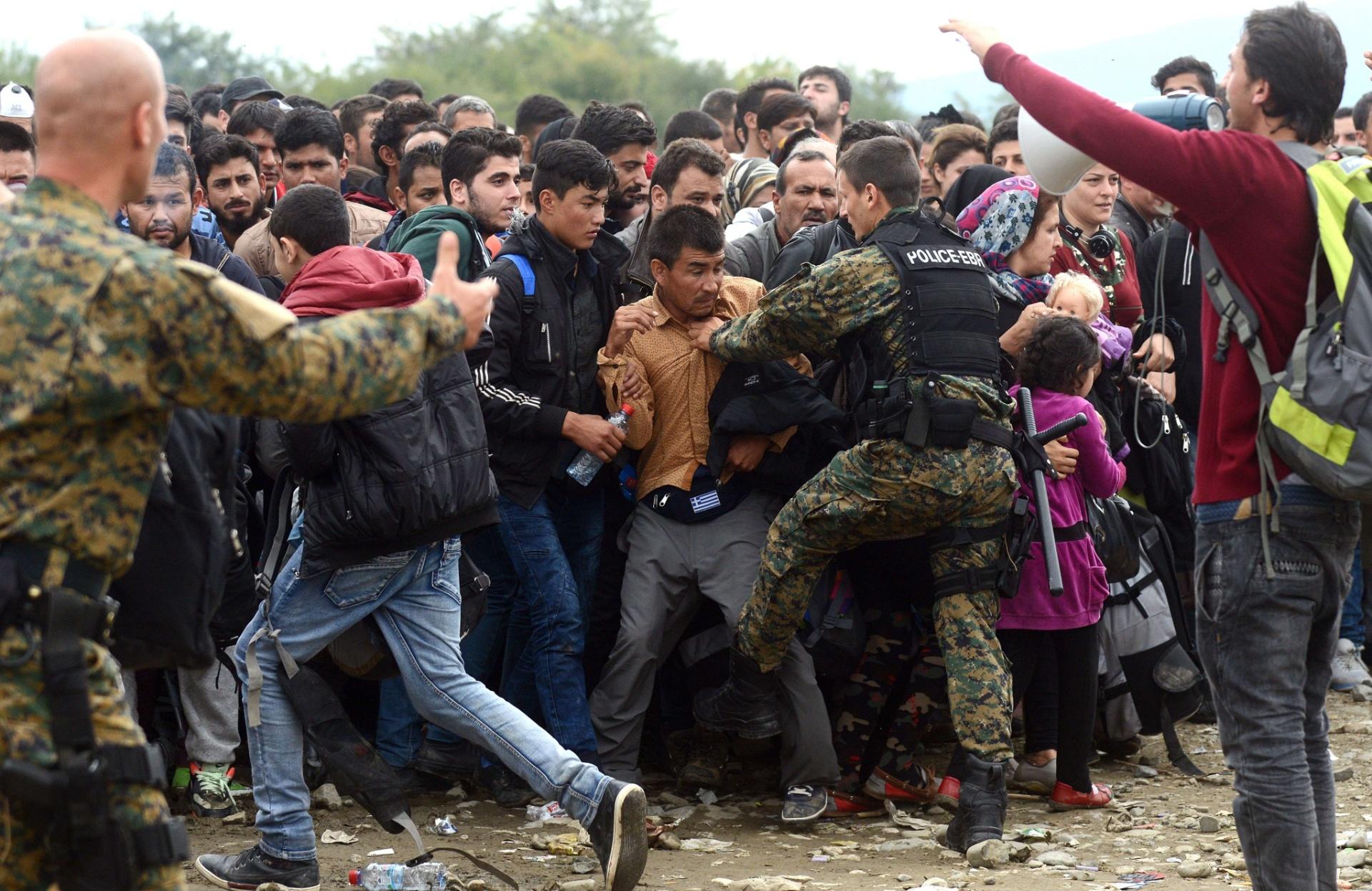 19.out.2015 - Policiais controlam entrada de refugiados em um acampamento na cidade de Gevgelija, na Macedônia, próxima a fronteira com a Grécia. Refugiados vindos principalmente da Síria chegam à Europa na tentativa de salvar suas vidas ao fugirem da guerra civil