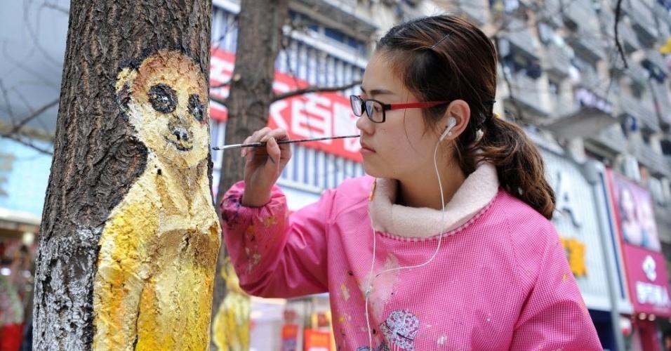 5.jan.2016 - Artista faz pintura em árvore de Chongqing, na China. As árvores da cidade ganharam grafites com ilustrações de animais