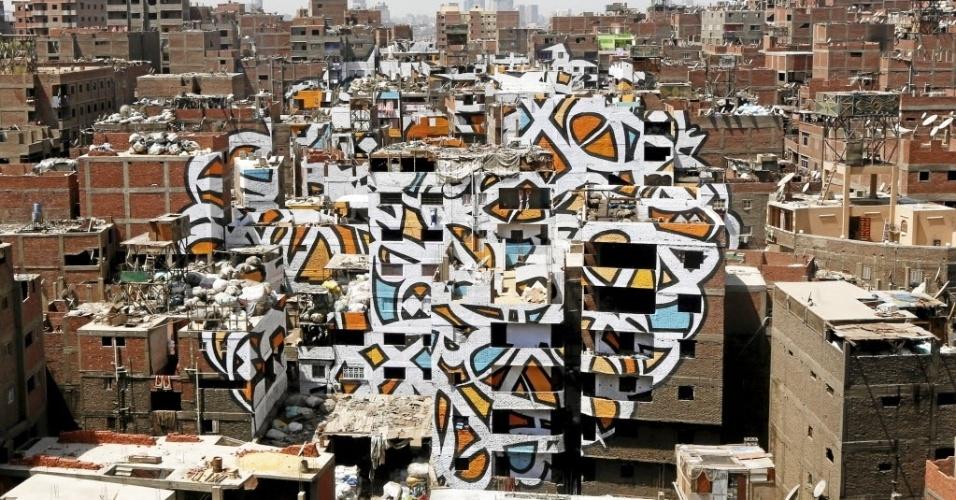 14.abr.2016 - Artista franco-tunisino El Seed pinta mural  nas paredes de casas em Zaraeeb, uma  região conhecida como ?Cidade do Lixo?, no leste do Cairo, Egito
