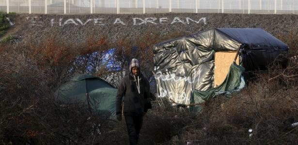 """Refugiado caminha entre abrigos próximos a mensagem que diz """"Nós temos um sonho"""", em Calais, na França"""