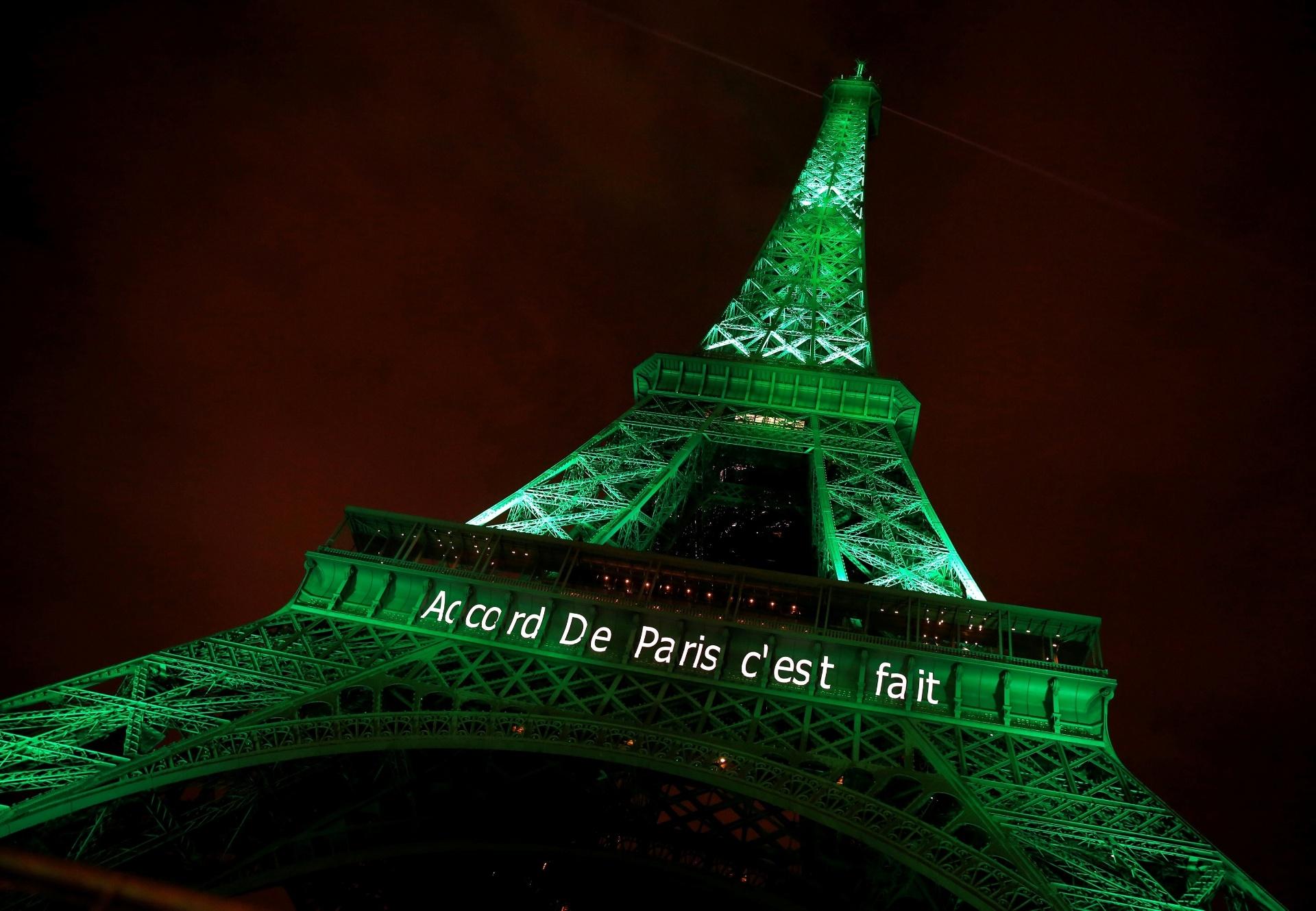 """4.nov.2016 - CONTRA MUDANÇAS CLIMÁTICAS - A Torre Eiffel é iluminada de verde com as palavras """"O Acordo de Paris está feito"""" para celebrar que a resolução entrou em vigor em tempo recorde, menos de um ano depois de ter sido fechada em Paris, na França. Ao todo, 195 países concordaram com o texto que visa combater às mudanças climáticas"""