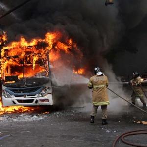 Bombeiros apagam fogo em ônibus que foi incendiado durante confronto entre a Polícia Militar e manifestantes
