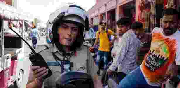 14.jun.2017 - A policial Saroj Chodhuary, membro da nova unidade feminina, escuta o rádio no mercado de Jaipur, na Índia - Chandan Khanna/AFP - Chandan Khanna/AFP