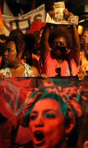 """20.mar.2018 - Mulher exibe recorte de jornal que se lê """"a voz da favela"""" durante ato que marca o sétimo dia de morte da vereadora Marielle Franco e do seu motorista Anderson Gomes realizado na Candelária, região central do Rio de Janeiro"""