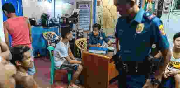 Policiais questionam homens que foram detidos por infrações menores no distrito de Tondo, em Manila, nas Filipinas - Hannah Reyes Morales/The New York Times - Hannah Reyes Morales/The New York Times