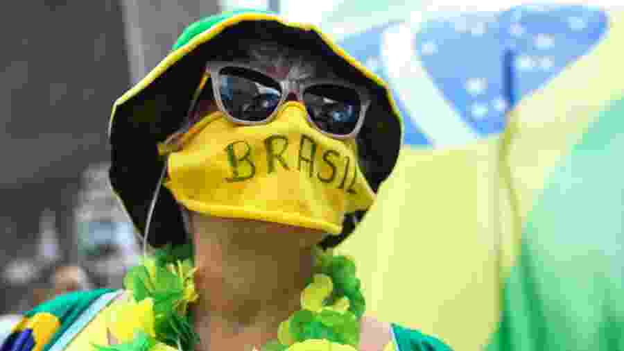 Mulher veste cores do Brasil e usa máscara durante pandemia do novo coronavírus - Alexandre Schneider/Getty Images