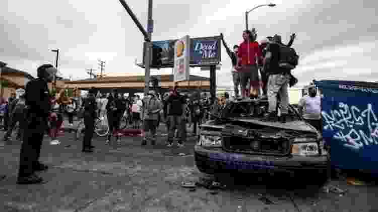 Manifestantes no topo de um carro da polícia queimado em Los Angeles, Califórnia - EPA - EPA