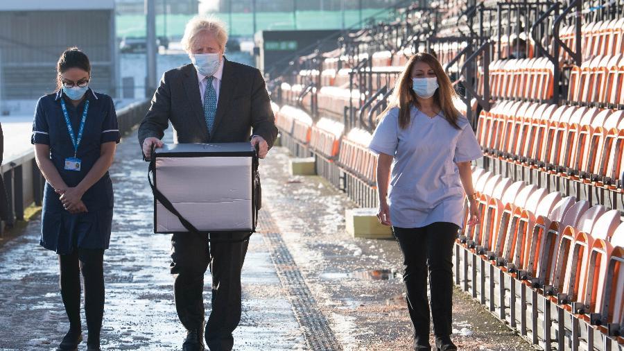 25.jan.2021 - O primeiro-ministro britânico, Boris Johnson, carrega vacinas que serão aplicadas em um centro de vacinação em Londres. O Reino Unido ultrapasso os 100.000 mortos por coronavírus - Stefan Rousseau/Reuters
