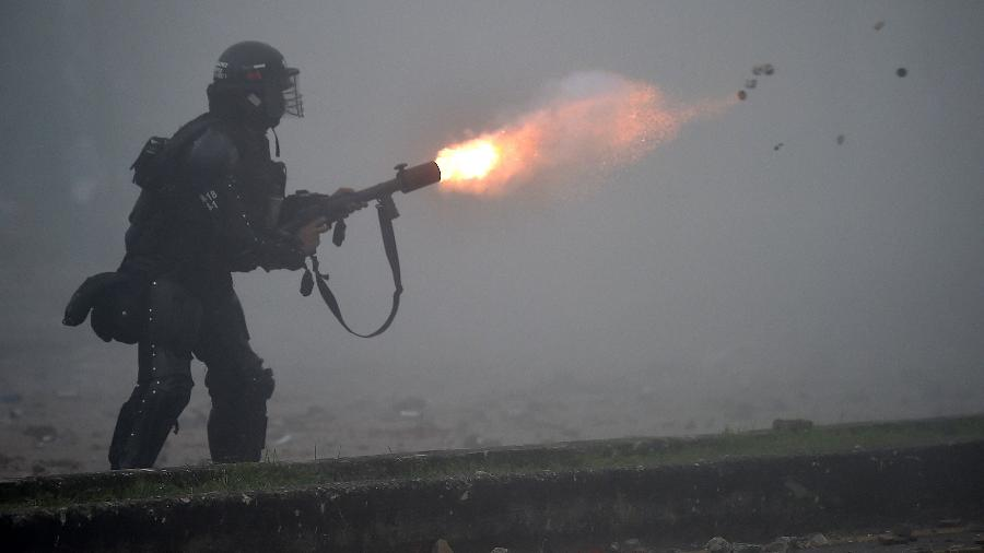 Policial dispara bombas de gás lacrimogênio para conter manifestantes em protesto na Colômbia - Luis Robayo/AFP