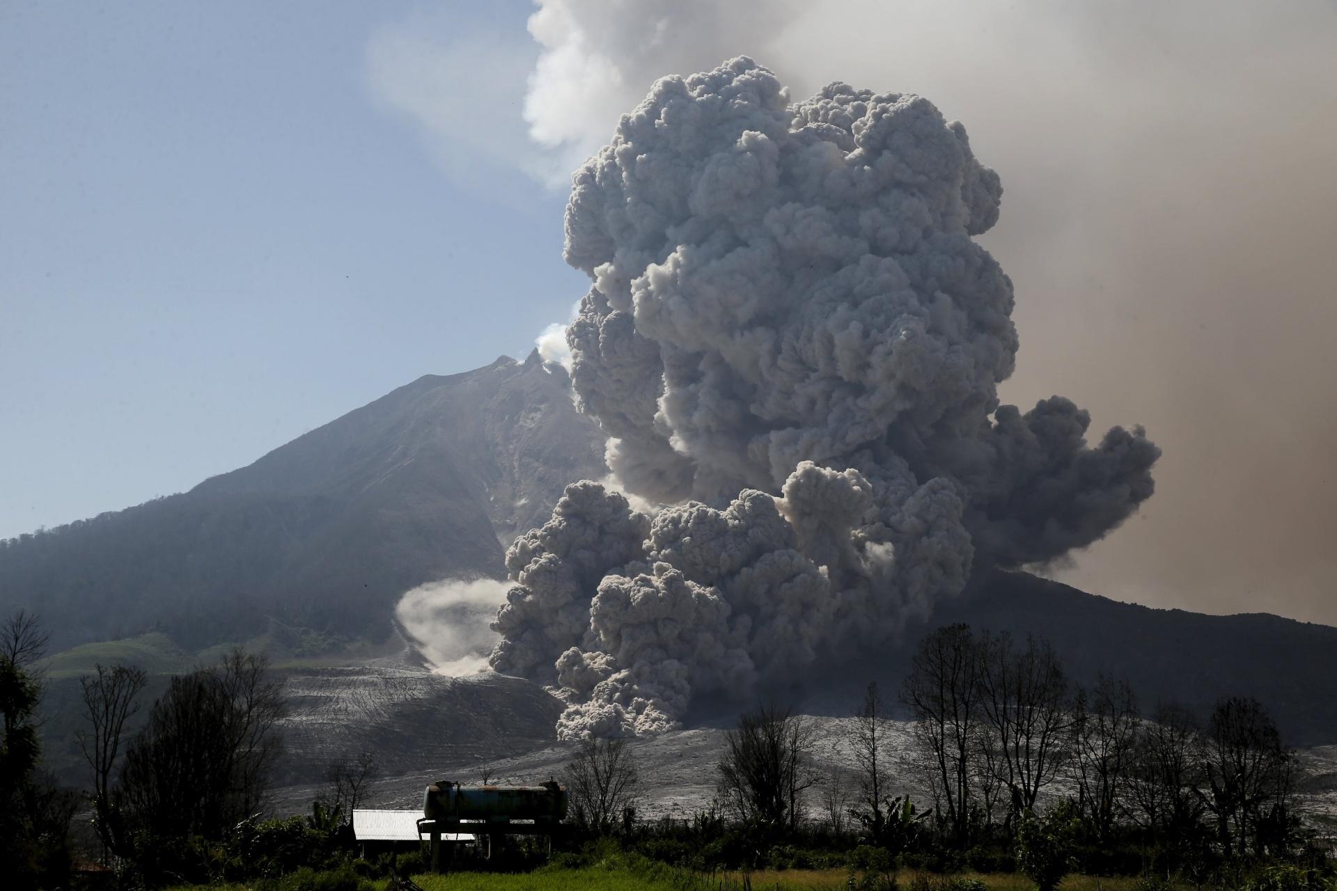 29.jun.2015 - Vulcão Sinabung expele cinzas durante erupção, vista do vilarejo de Beras Tepu, no norte de Sumatra, na Indonésia, nesta segunda-feira (29). Mais de 10 mil pessoas de 12 vilarejos deixaram suas casas e foram removidas para campos de refugiados, devido a erupção do vulcã