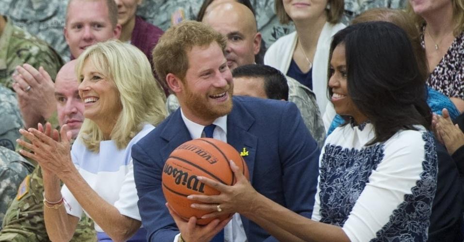 28.out.2015 - O príncipe britânico Harry segura uma bola de basquete para primeira-dama dos EUA, Michelle Obama, em um jogo disputados por soldados feridos em combate, em Fort Belvoir, na Virginia (EUA). O príncipe é o patrono torneio Invictus, uma competição internacional para os membros de serviços armados feridos em combate