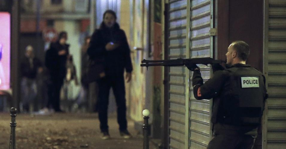 13.nov.2015 - Um policial francês aponta arma enquanto procura os atiradores que atacaram o restaurante Le Petit Cambodge em Paris, na França. Tiroteios e explosões aconteceram na noite desta sexta-feira (13) na capital francesa. A polícia relatou ao menos duas explosões nas proximidades do estádio Stade de France, onde o presidente francês, François Hollande, acompanhava um amistoso da seleção francesa