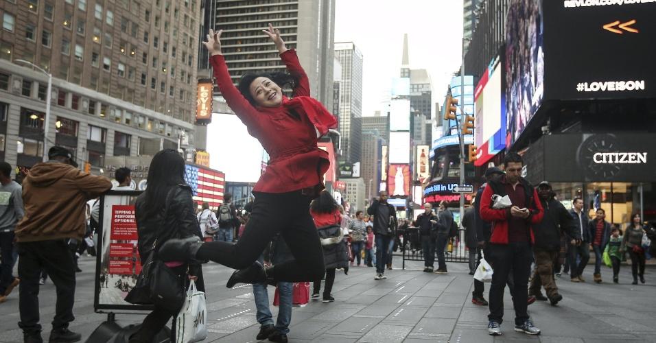 24.dez.2015 - turista salta para fotografia na Times Square, em NY; cidade tem calor recorde no Natal e fica sem neve
