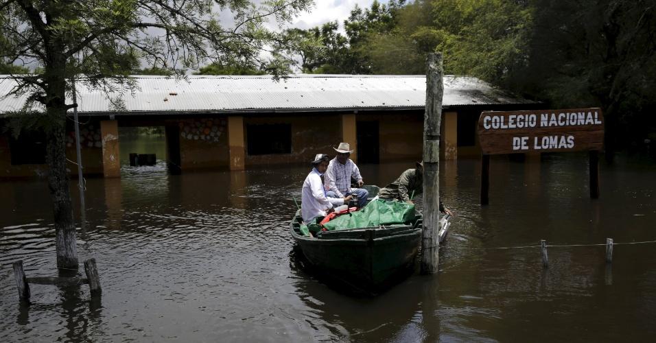 5.jan.2016 - Moradores usam barco para se locomover próximo ao Colégio Nacional de Lomas, na cidade de Alberdi, no Paraguai, inundada pela cheia do rio Paraguai