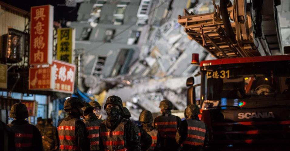 7.fev.2016 - 7.fev.2016 - Equipes de resgate aguardam no local onde um edifício que desabou em decorrência do terremoto que atingiu a região de Tainan, no sul de Taiwan, na madrugada deste sábado. O tremor de magnitude 6,4 causou a morte de pelo menos 18 pessoas, sendo que mais de 150 continuam soterradas sob um prédio de 17 andares que desabou