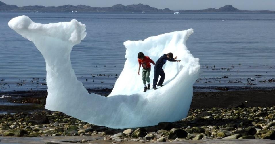 13.jun.2016 - Crianças brincam em pedaço de iceberg na praia de Nuuk, na Groelândia