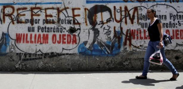 """Pedestre passa por mural que mostra grafite que diz """"referendo"""" em Caracas, na Venezuela"""