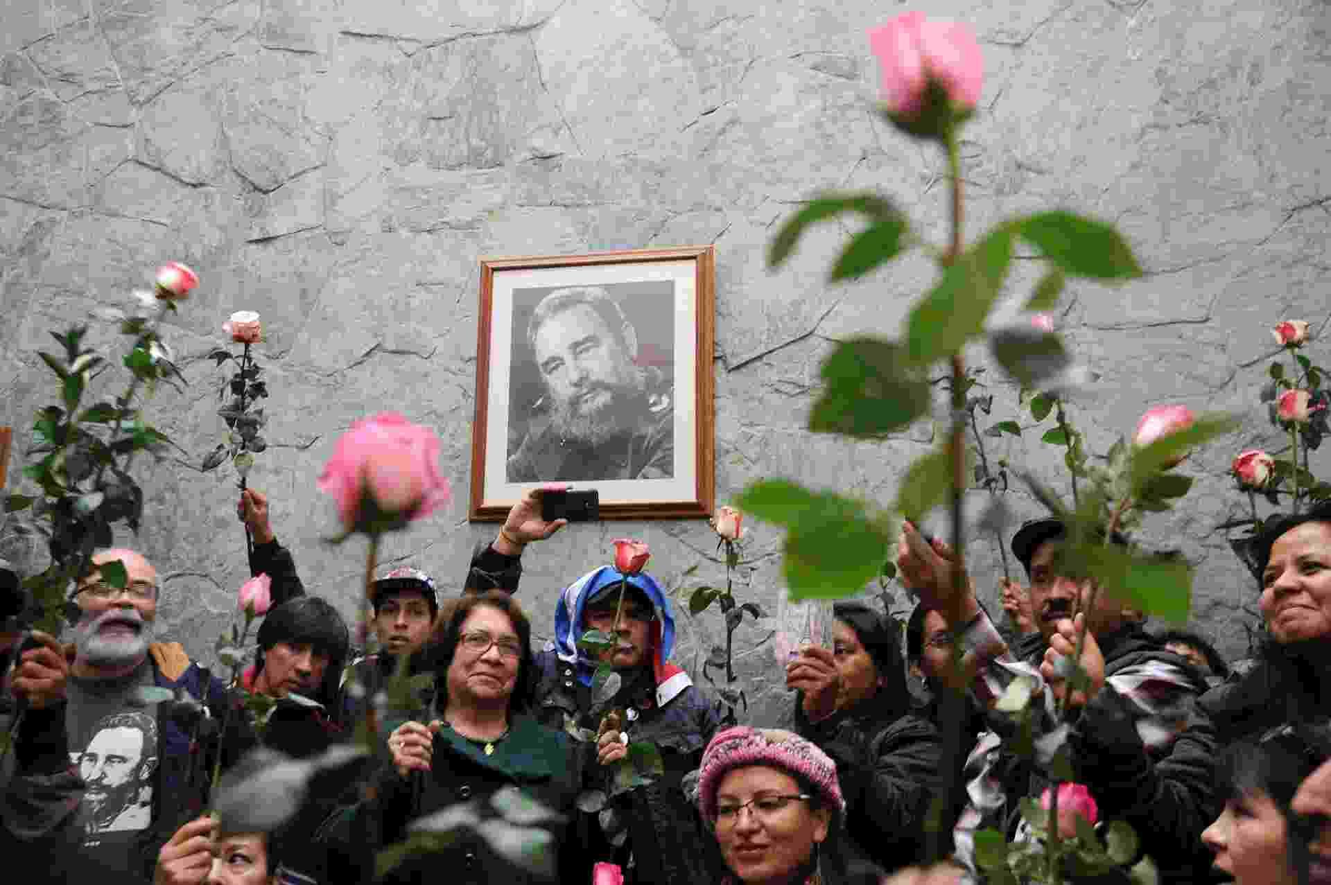 27.nov.2016 - Pessoas seguram rosas em frente a um porta-retrato de Fidel Castro na embaixada de Cuba na Colômbia - Guillermo Legaria/AFP