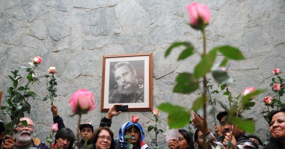 27.nov.2016 - Pessoas seguram rosas em frente a um porta-retrato de Fidel Castro na embaixada de Cuba na Colômbia