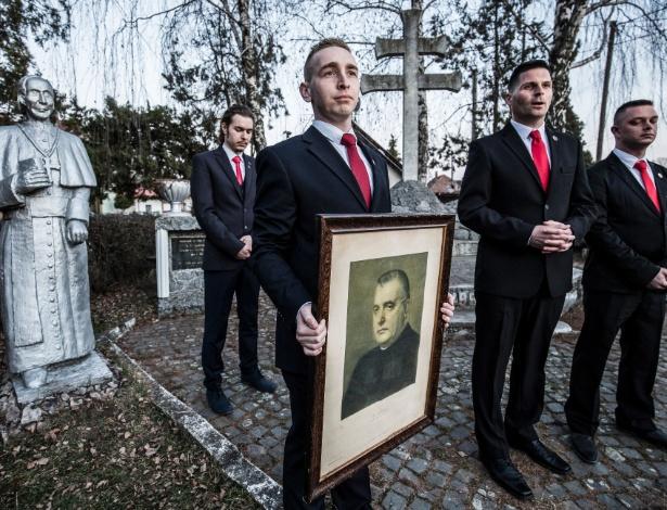 Robert Svec, líder do Movimento de Renascimento Eslovaco, segura retrato de líder fascista Josef Tizo, em Cakajovce, na Eslováquia - Akos Stiller/The New York Times