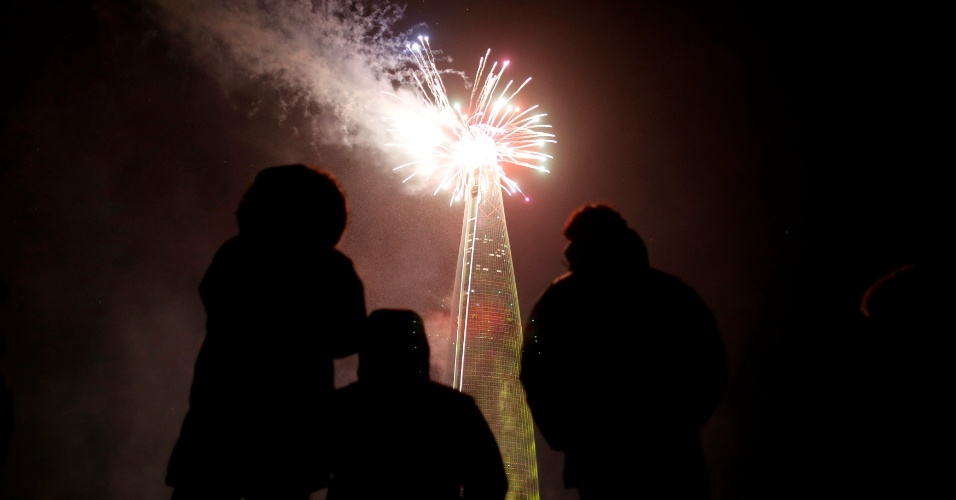 Sul-coreanos observam show pirotécnico sobre arranha-céu durante celebração do Ano-Novo em Seul